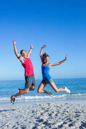 fit woman: Happy couple jumping together at the beach