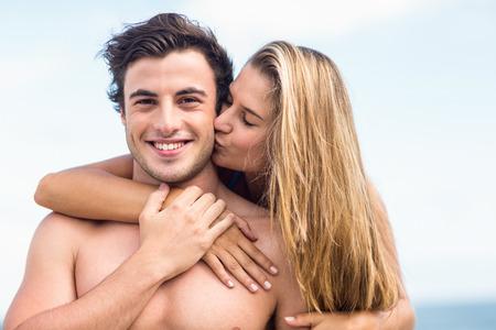 enamorados besandose: Apuesto hombre recibe beso de su gilfriend en la playa
