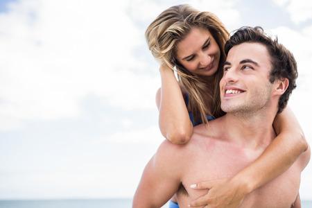 Handsome Mann mit piggy zurück zu seiner Freundin am Strand