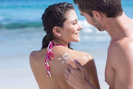 putting on: Handsome man putting sun tan lotion on his girlfriend at the beach