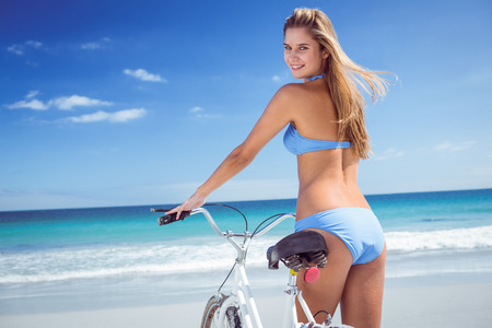 human sexual activity: Pretty blonde woman going on a bike ride at the beach Stock Photo