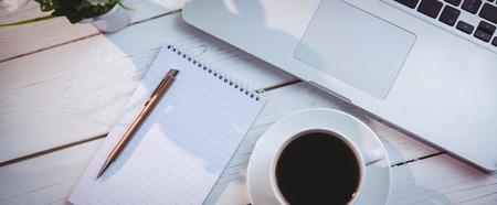 Overhead-Schuss von Laptop und Notizblock auf einem Schreibtisch Standard-Bild