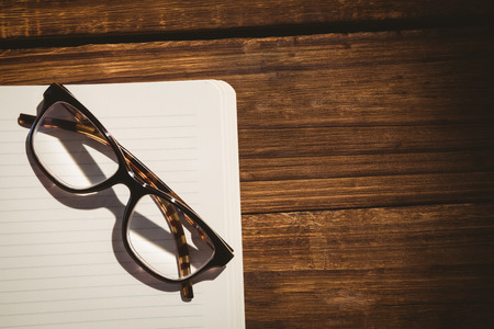 reading glasses: Empty notepad with reading glasses on a desk Stock Photo