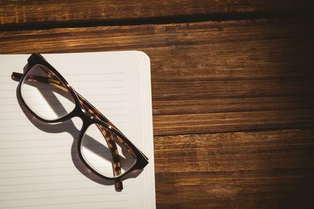 gafas: Libreta vac�a con gafas de lectura en un escritorio