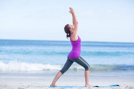 beach mat: Brunette doing yoga on exercise mat at the beach