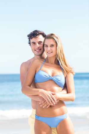 sexy couple on beach: Happy couple in swimsuit looking at camera and embracing at the beach