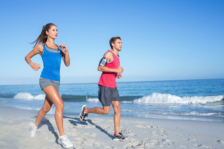 handsome young athletic: Happy couple running together beside the water at the beach
