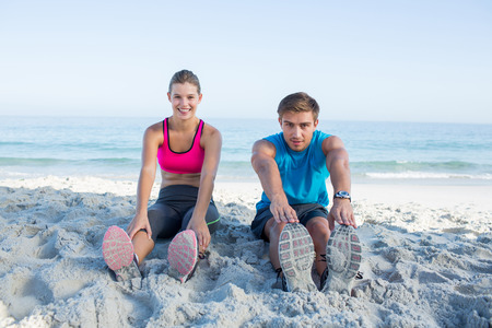 touching toes: Happy couple stretching together beside the water at the beach