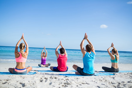 Amici facendo yoga insieme alla loro insegnante in spiaggia Archivio Fotografico
