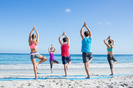 Friends doing yoga together with their teacher at the beach Stock Photo