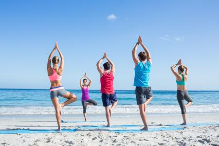 beach yoga: Friends doing yoga together with their teacher at the beach Stock Photo
