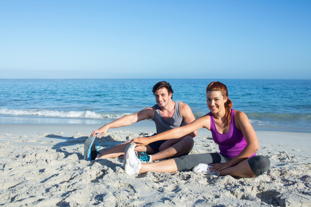 fitness couple: Happy couple stretching together beside the water at the beach
