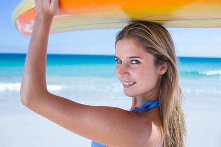 sexual activities: Pretty blonde woman holding surf board at the beach