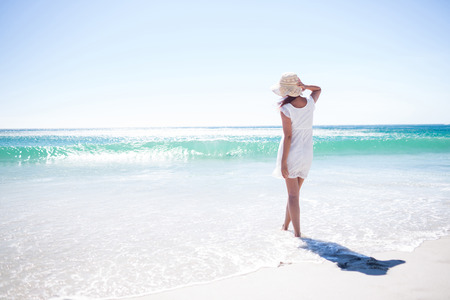 relaxing: Pretty brunette wearing straw hat and walking in the water at the beach