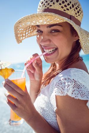 cocteles: Brunette sonriente con el sombrero de paja y beber un c�ctel en la playa