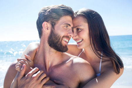sexy couple on beach: Happy couple hugging and smiling at each other at the beach