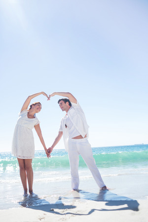 Happy couple forming heart shape with their hands at the beach