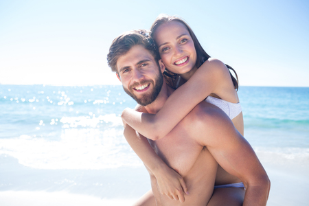 bikini couple: Handsome man giving piggy back to his girlfriend at the beach