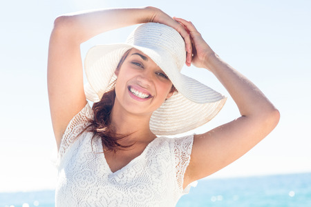 sunhat: Pretty brunette wearing sunhat and looking at camera at the beach Stock Photo