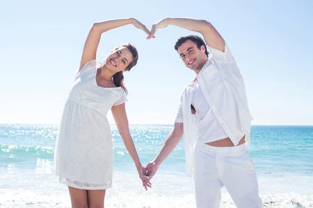 parejas felices: Feliz pareja formando forma de corazón con sus manos en la playa Foto de archivo
