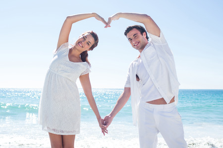 happy young couple: Happy couple forming heart shape with their hands at the beach