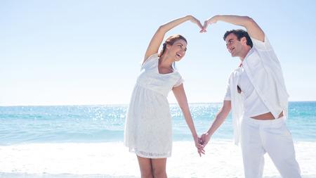 mujer enamorada: Feliz pareja formando forma de coraz�n con sus manos en la playa Foto de archivo