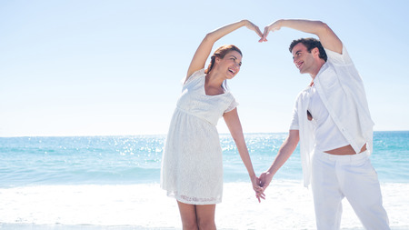 escapism: Happy couple forming heart shape with their hands at the beach