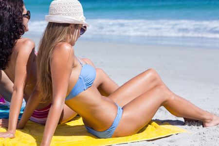 woman towel: Beautiful women sitting on the towel at the beach