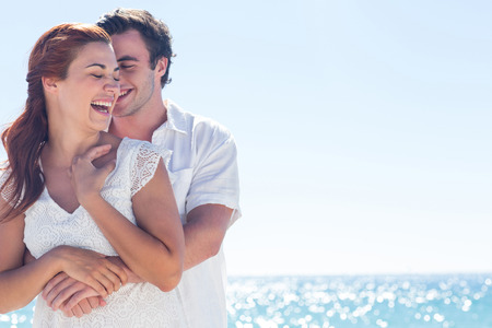happy young woman: Happy couple hugging and laughing together at the beach