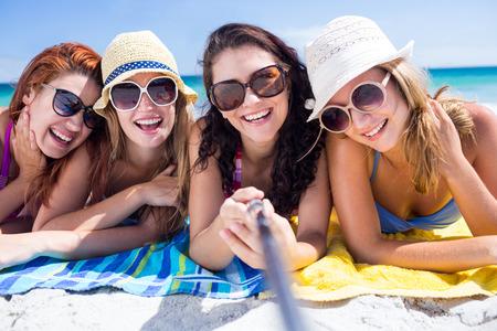 sonne: Gl�ckliche Freunde mit Sonnenbrille und unter selfie am Strand
