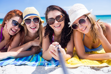 sunny beach: Happy friends wearing sun glasses and taking selfie at the beach