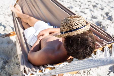 hombres guapos: Hombre guapo descansando en la hamaca en la playa
