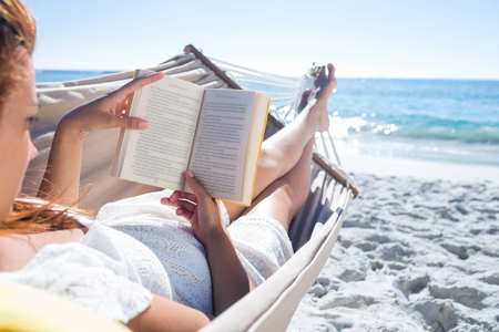 sunny beach: Brunette reading a book while relaxing in the hammock at the beach Stockfoto