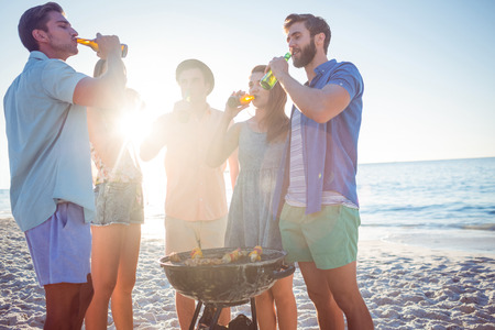 summer  sunlight: Happy friends doing barbecue and drinking beer at the beach