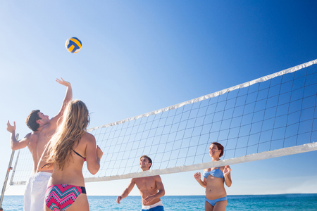female friends: Group of friends playing vollerball at the beach Stock Photo