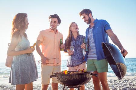 barbecue: Amigos felices que hacen barbacoa y bebiendo cerveza en la playa
