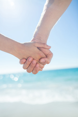 escapism: Couple walking hand in hand at the beach