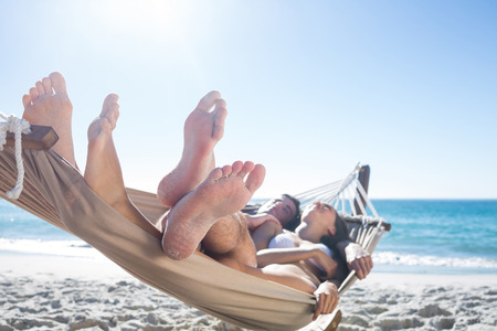 happy young woman: Happy couple napping together in the hammock at the beach