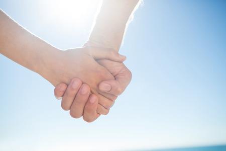 tomados de la mano: Pareja caminando de la mano en la playa