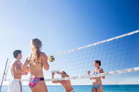pelota de voleibol: Grupo de amigos que juegan a voleibol en la playa Foto de archivo