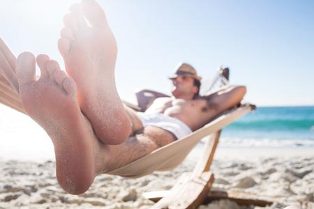 relaxando: Homem bonito que descansa na rede na praia