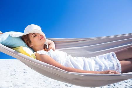 hammock: Pretty morena se relaja con su sombrero de paja en la hamaca en la playa