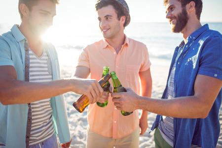 hombres guapos: Hombres hermosos que tuestan en la playa Foto de archivo