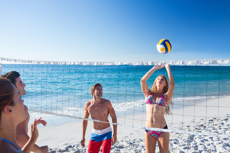 man beach: Group of friends playing volleyball at the beach Stock Photo