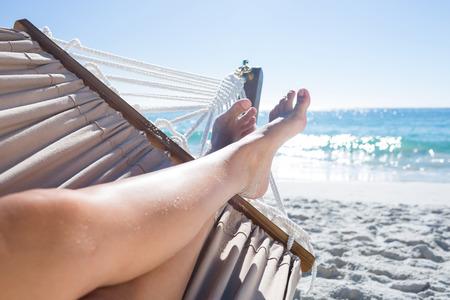 Vrouw ontspannen in de hangmat op het strand