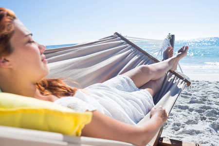 escapism: Brunette relaxing in the hammock at the beach