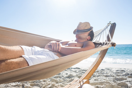 sunshine: Hombre guapo descansando en la hamaca en la playa