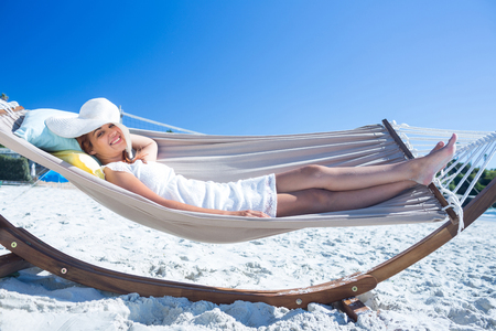sombrero: Pretty brunette relaxing with her straw hat in the hammock at the beach