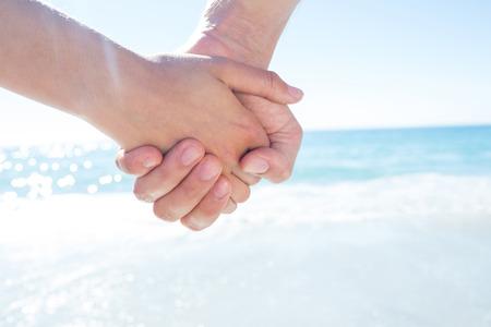 manos entrelazadas: Pareja caminando de la mano en la playa