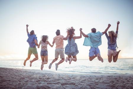 fiesta: Amigos felices tomados de la mano y saltando en la playa Foto de archivo